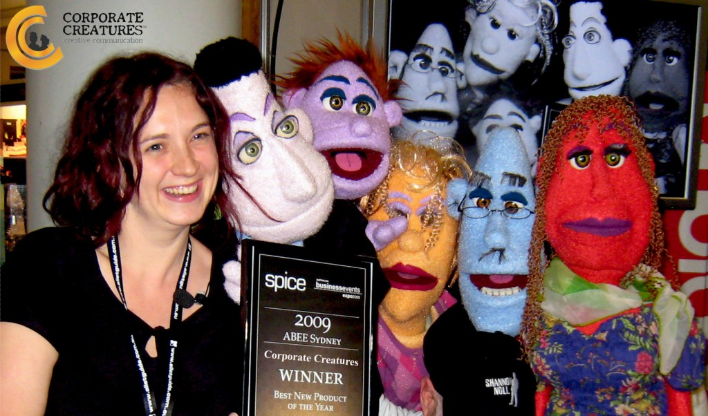 "Spice Magazine representative, Gwen O'Toole presenting the Corporate Creature puppets with the ABEE ""Best New Product of the Year"" Award"